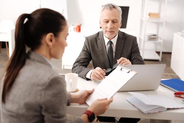 Vriendelijke baas zit op zijn werkplek tegenover secretaris scherm van computer kijken terwijl glimlach op zijn gezicht