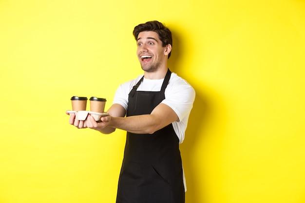 Vriendelijke barista in zwart schort die afhaalmaaltijden geeft, twee kopjes koffie vasthoudt en glimlacht, staande over gele achtergrond.