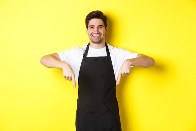 Vriendelijke barista in zwart schort die met de vingers naar beneden wijst, je logo-banner laat zien, staande over de gele muur
