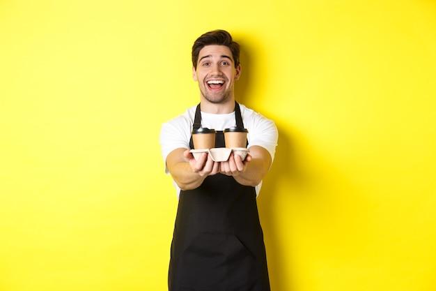 Vriendelijke barista in zwarte schort die afhaalbestelling geeft, twee kopjes koffie vasthoudt en glimlacht, staande over gele achtergrond