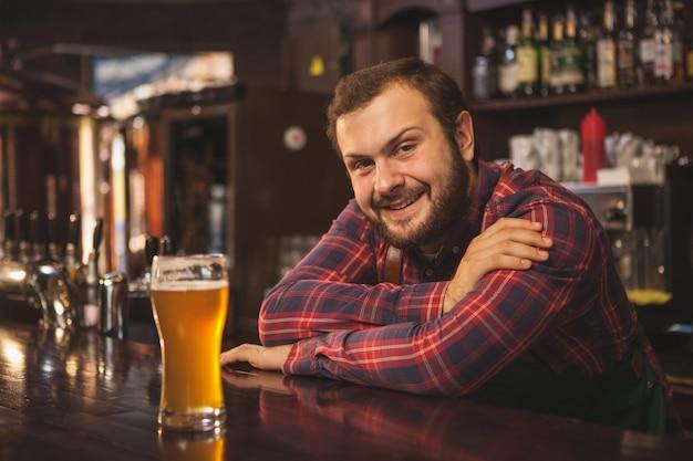 Vriendelijke bebaarde barman lacht vrolijk naar de camera en geniet van het werken in zijn biercafé