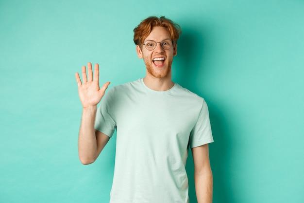 Vriendelijke bebaarde man in glazen die hallo zegt, hand zwaait om je te begroeten en te verwelkomen, vrolijk staat en glimlacht over turkooizen achtergrond.