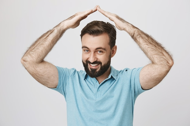 Vriendelijke bebaarde volwassen man dak gebaar boven het hoofd maken