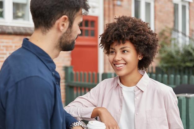 Vriendelijke, beste vrienden van gemengd ras genieten van een gesprek met elkaar