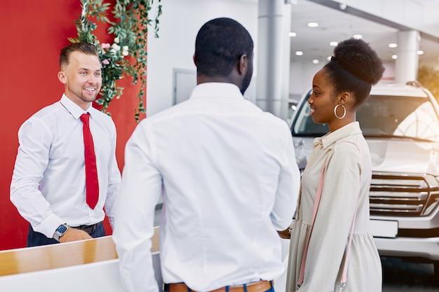 Vriendelijke blanke man beheerder en adviseur van dealerbedrijf verwelkomt klanten