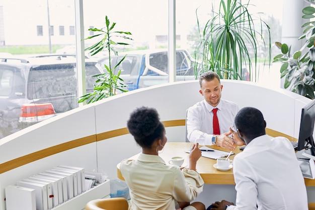Vriendelijke blanke man manager behandelt klanten met heerlijke koffie bij dealer