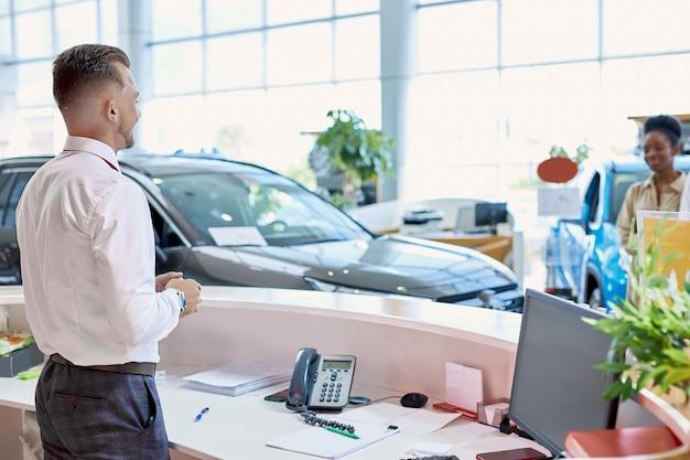 Vriendelijke blanke manager groet klanten in autosalon