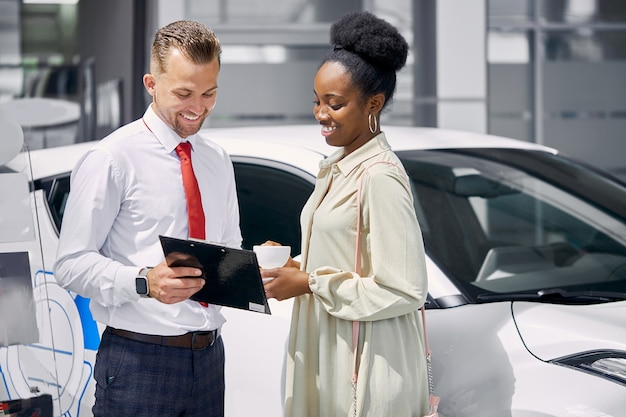 Vriendelijke blanke verkoper praat met zwarte klant vrouw