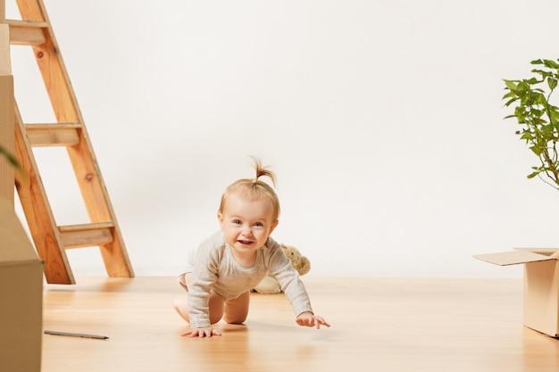 Vriendelijke blauwe ogen babymeisje, zittend op de vloer binnenshuis