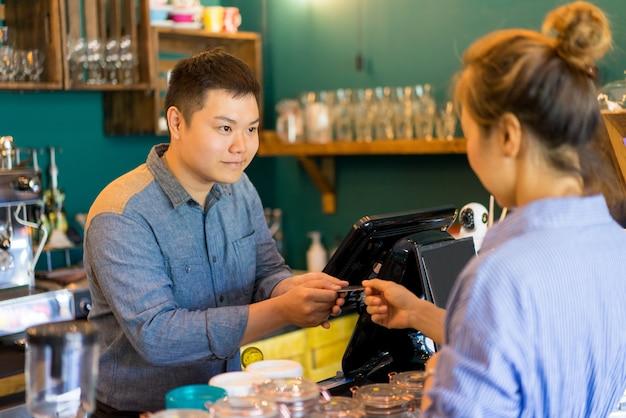 Vriendelijke café kassier accepteren betaling van klant en het nemen van een creditcard.