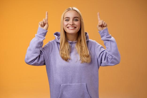 Vriendelijke charismatische energieke jonge blonde europese vrouw in gezellige hoodie handen omhoog wijsvinger presenteren geweldige reclame glimlachend product, oranje achtergrond gelukkig aanbevelen.