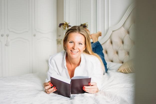 Vriendelijke charmante blondevrouw met lang eerlijk haar in het boek van de vrijetijdskledingslezing op bed in helder rijk binnenland