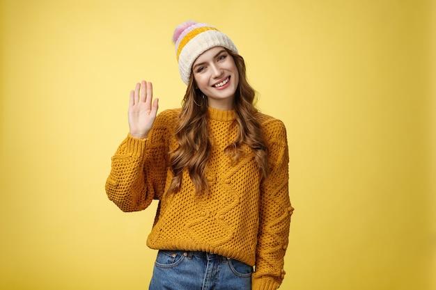 Vriendelijke charmante lachende jonge vrouw kantelend hoofd uitgaande blik zwaaiende hand hallo hallo gebaar groet...