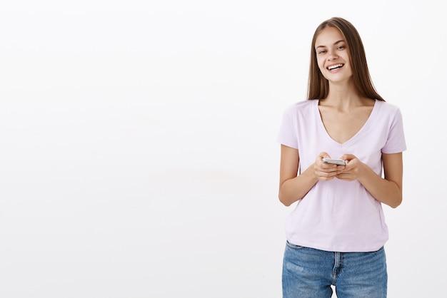 Vriendelijke charmante vrouwelijke kantoormedewerker in schattige blouse glimlachend vreugdevol vasthouden van smarpthone terwijl notities maken in apparaat beleefd met klant praten