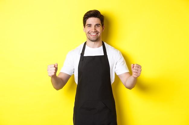 Vriendelijke coffeeshop ober die zich met opgeheven handen bevindt, plaats voor uw teken of logo, die zich over gele achtergrond bevindt.