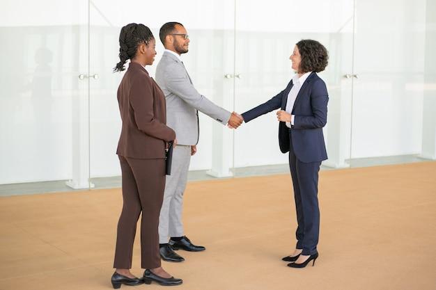 Vriendelijke collega's begroeten elkaar