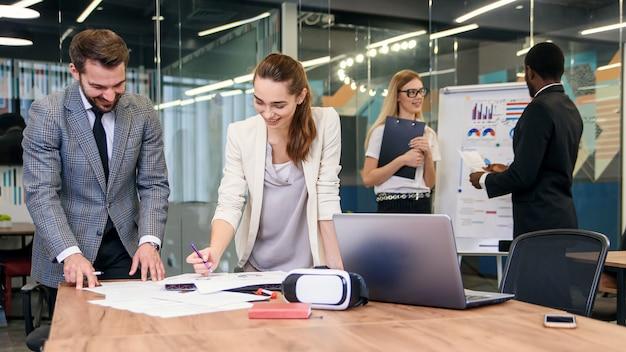 Vriendelijke collega's bespreken tijdens de werkdag hun gezamenlijke businessplan.