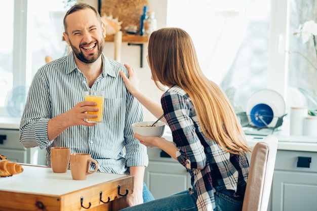 Vriendelijke dame die een schouder van een man aanraakt en hem ziet lachen Premium Foto