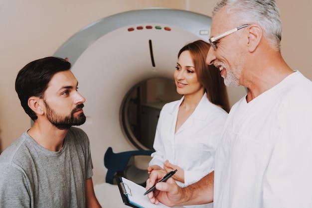 Vriendelijke doc en verpleegster praten met de patiënt vóór de ct.