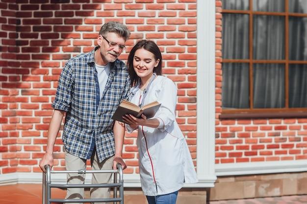 Vriendelijke dokter, verpleegster die buitenshuis zorgt voor een zieke oudere vrouw in een rolstoel