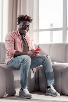 Vriendelijke emoties. vrolijke mannelijke persoon zittend op de bank en luisteren naar muziek