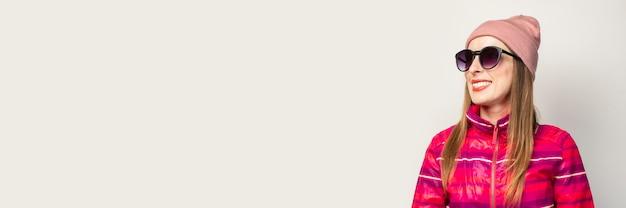 Vriendelijke emotionele jonge vrouw in glazen, hoed en roze colbert lacht