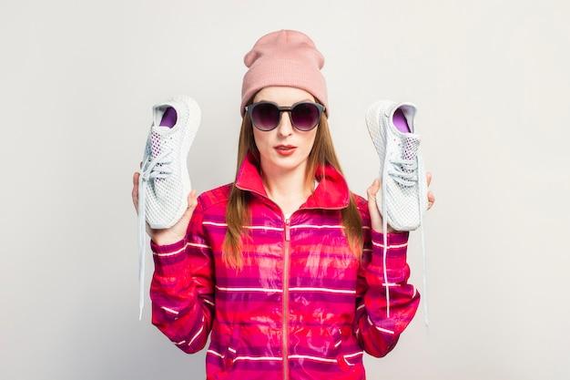 Vriendelijke emotionele jonge vrouw met bril, hoed en roze sportjasje met een ernstig gezicht houdt modieuze sneakers op wit oppervlak