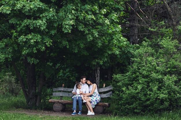 Vriendelijke en gelukkige familie rusten op een houten bankje onder de esdoorn.