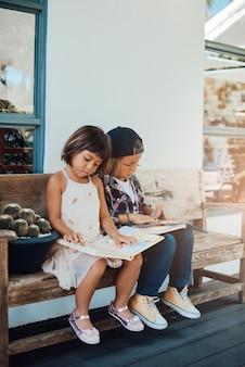 Vriendelijke en schattige jongen en zijn zus hebben een goede tijd samen met het lezen van een boek op een bankje in het park.
