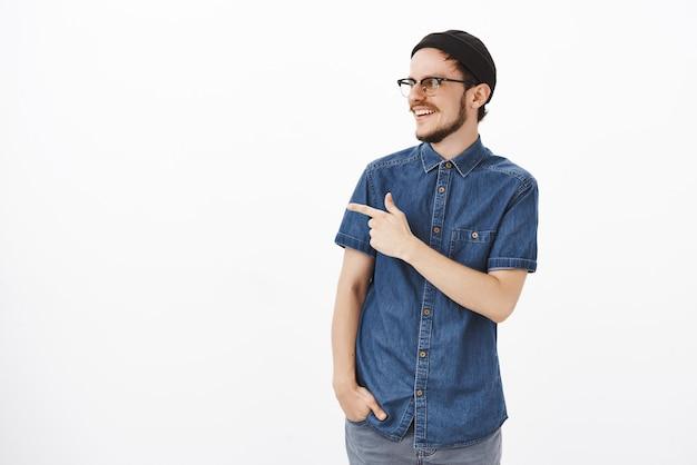 Vriendelijke en vrolijke knappe man met baard in bril en hipster zwarte muts draaien en wijzen naar links zorgeloos kijken naar man die geweldige trucs op skateboard maakt