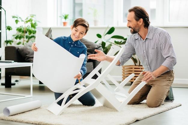 Vriendelijke enthousiaste vader die met zijn glimlachende tienerzoon op de grond zit en samen met hem een nieuwe stoel monteert