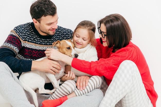 Vriendelijke familie omhelst elkaar en vleit hun hond, veel plezier, poseren samen tegen wit