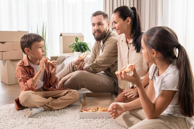 Vriendelijke familie pizza eten in een nieuw huis