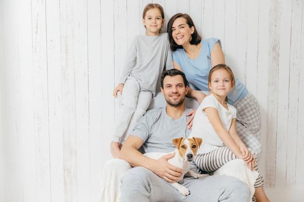 Vriendelijke familie poseert samen tegen wit: twee kleine zusjes, vader, moeder en hun huisdier