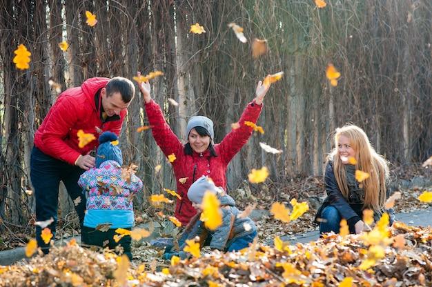 Vriendelijke familie tijdens een wandeling tijdens de val van de bladeren in het park