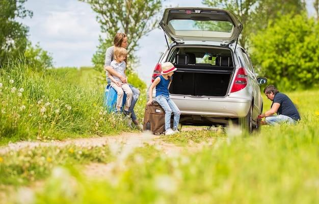 Vriendelijke familie verwisselt de band van de auto