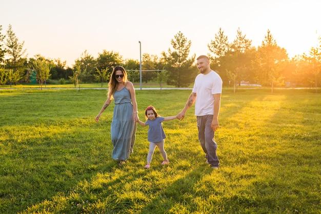 Vriendelijke familie wandelen in het park en samen plezier hebben
