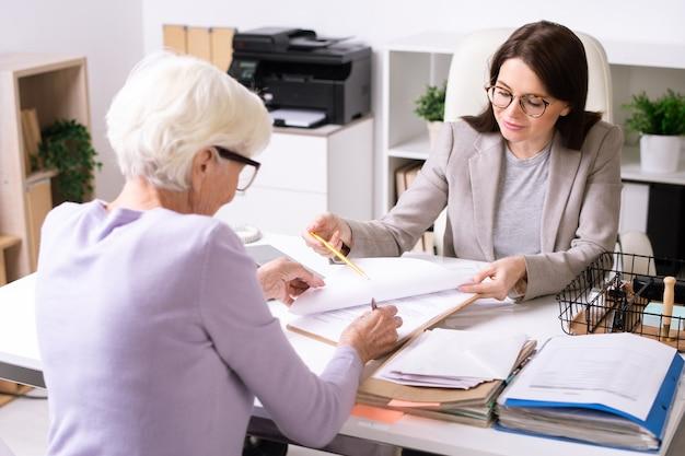 Vriendelijke financieel adviseur die met senior vrouw werkt en plaats toont voor ondertekening in document