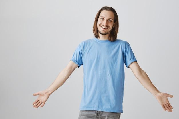 Vriendelijke gelukkige hipster man spreidde zijn handen, verwelkomt gasten en glimlachte