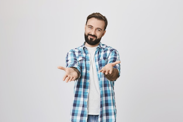Vriendelijke gelukkige jonge man wijzende handen naar je tevreden