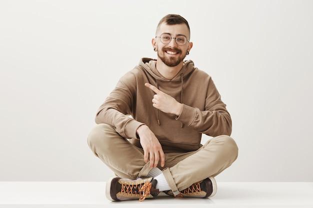 Vriendelijke, gelukkige man zit op de vloer en wijst de linker bovenhoek van de vinger, richtinggevend