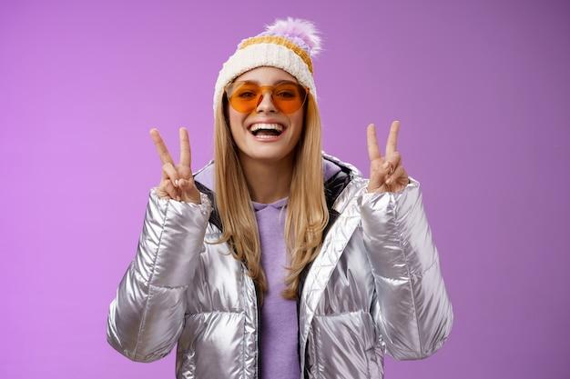 Vriendelijke gelukkige optimistische mooie blonde vrouw in zonnebril zilveren stijlvolle jas winter hoed vrede overwinning gebaar genieten van besneeuwde vakantie krijgen buiten hotel genieten van skiën, paarse achtergrond.