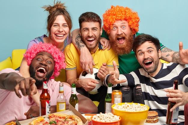 Vriendelijke gelukkige vier jonge mannen en een vrouw omhelzen en kijken vreugdevol naar het scherm van tv, genieten van televisie kijken en grappige film, bal vasthouden voor voetbal, veel plezier thuis.