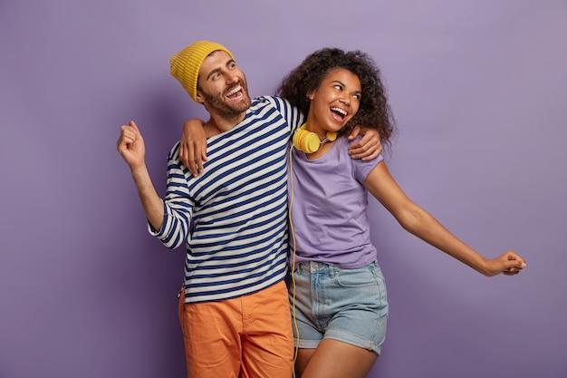 Vriendelijke gemengd ras vrouw en man omhelzen en dansen vreugdevol