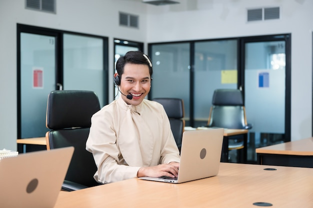 Vriendelijke glimlach operator aziatische homo-agent met headset die met laptop werkt aan klantoverleg op kantoor bij callcenter
