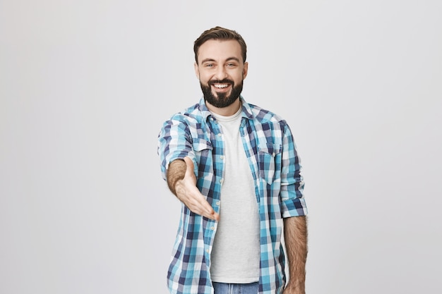 Vriendelijke glimlachende man hand uit te steken voor handdruk, groetgebaar