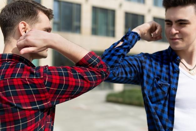Vriendelijke glimlachende man sociale afstand houden, elkaar begroeten door ellebogen te stoten