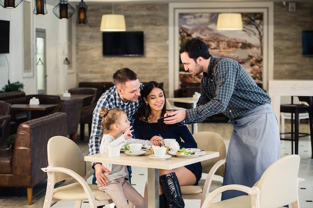 Vriendelijke glimlachende ober die orde nemen bij lijst van familie die diner samen hebben