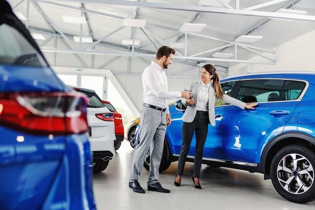 Vriendelijke, glimlachende vrouwelijke verkoper die gloednieuwe auto aan een klant toont terwijl hij in autosalon staat
