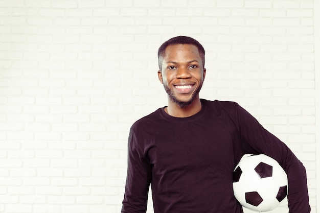Vriendelijke glimlachende zwarte man met een voetbal